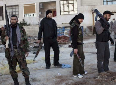 Free Syrian Army fighters gather near a building hit by a Syrian Army tank in Idlib, north Syria, on Sunday