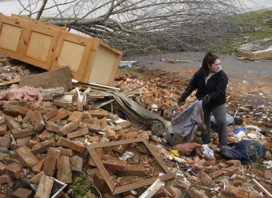 Hannah Rechel, from Dent, Ohio, helps recover personal items from debris after a tornado struck on Friday.