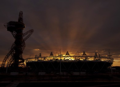 The sun sets behind the Olympic stadium in London yesterday.