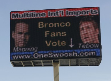 An electronic billboard located over a memorabilia store in north Denver urges fans to cast a ballot for either Peyton Manning, shown left, or Tim Tebow as the NFL quarterback for the Denver Broncos.