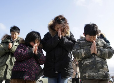 A family observes a moment of silence by the remains of a disaster centre in an area devastated by the tsunami