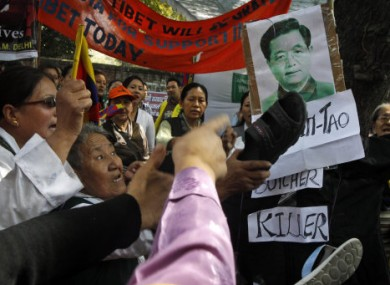 Tibetan exiles strike an image of Chinese President Hu Jintao during a demonstration in India on Saturday.