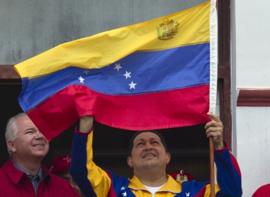 Chavez with a Venezuelan flag at his presidential palace earlier today