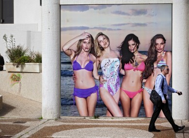 An Israeli walks past an advertising displayed on a main street in Tel Aviv, Israel, on Monday, March 19, 2012