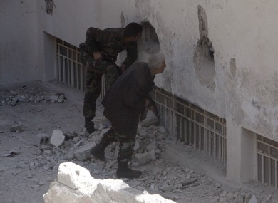 Syrian army soldiers search a building in Damascus for rebel fighters