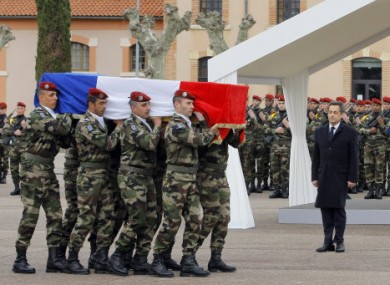 President Sarkozy stands by soldiers carrying a coffin during a ceremony to pay homage to the three soldiers.