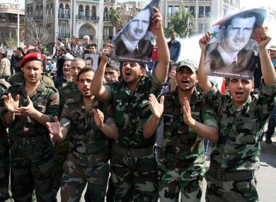 Syrian army soldiers hold pictures of Bashar al-Assad during a rally in Damascus