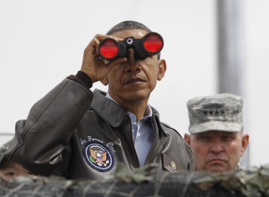 Obama looking through binoculars to see North Korea from the demilitarised zone today.