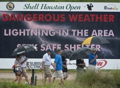 Patrons head for cover during a lightning delay in yesterday's Shell Houston Open first round.