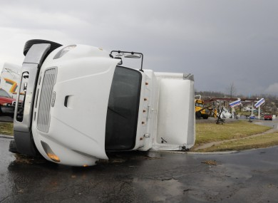 A truck lies on its side in front of the remains of a gas station in Henryville