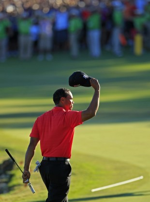 Woods salutes the crowd on the 18th.