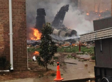 The burning fuselage of the jet lies smoldering after crashing into the houses