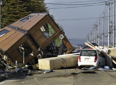 A man walks by a collapsed house and debris at Sendai Port in Sendai following last year's tsunami. New government reports say a similar quake could result in an even larger tidal wave.