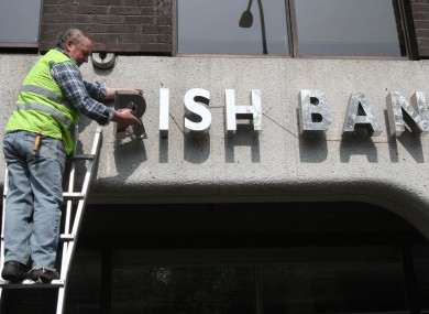 A workman removes the signage from the former Anglo Irish Bank HQ in Dublin