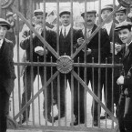 Crew members of Titanic who were detained as possible witnesses - there was a delay in sending the wire to tell them they could leave of their own volition. Here they are looking through closed dock-gates at Plymouth on 4 May 1912. (Topham/Topham Picturepoint/PA Images)