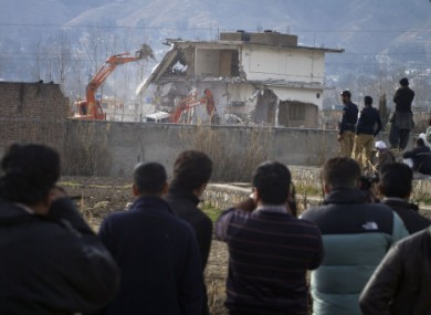 Media and locals watch as the Abbottabad compound Bin Laden was found in is demolished in February 2012.