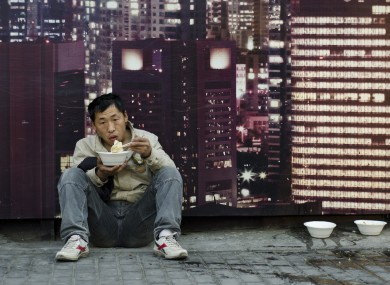A migrant worker has a meal in front of a billboard advertising a real estate project in Shanghai.