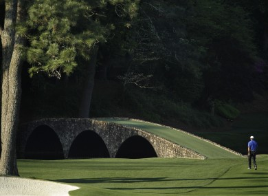 iger Woods walks towards the Ben Hogan Bridge on the 12th fairway during a practice round for t