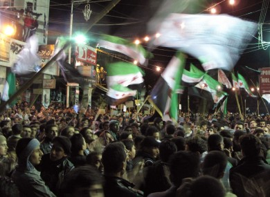 Syrians wave revolutionary flags and chant slogans at a night protest against President Bashar Assad in a neighborhood of Damascus