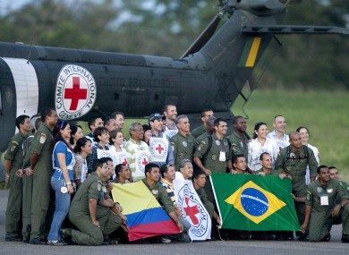 Crew members of a Brazilian army helicopter and International Red Cross members, pose for pictures after participating in a rescue operation of hostages released by Farc