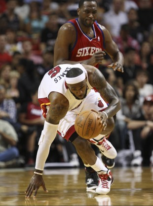 LeBron James, foreground, attempts to stay on his feet as he breaks for the basket trailed by Philadelphia 76ers forward Elton Brand.