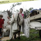 Deeann Powell recovers items from the trailer that a tornado lifted from her driveway to her neighbour's yard in Arlington, Texas. (AP Photo/Kim Johnson Flodin/PA Images)