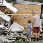 Bill Brangers, right, and Benjamin Powell, 5, left, look at the trailer that a tornado lifted from the Powell's driveway to a neighbour's garden two doors down in Arlington, Texas. (AP Photo/Kim Johnson Flodin/PA Images)