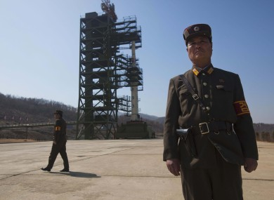 North Korean soldiers stand in front of the country's Unha-3 rocket before launch