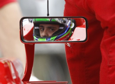 Ferrari F1 driver Felipe Massa looks out his rear-view mirror, as his team work on his car in the pit lane during practice for this weekend's Chinese Grand Prix in Shanghai.