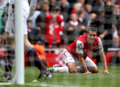 Arsenal's Robin van Persie kneels dejected after his shot on goal hits the side netting.