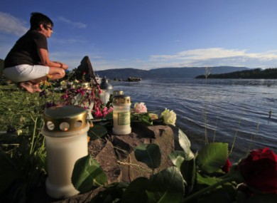 A woman looks towards Utoya and sits among floral tributes to the victims of the July 2011 attack.