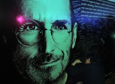 A man writes a message on a board erected in dedication to Steve Jobs following his passing