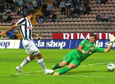 Juventus's Mirko Vucinic scores past Cagliari goalkeeper Michael Agazzi.
