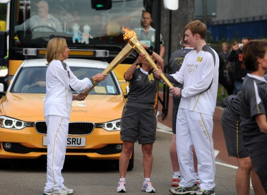 Torchbearers in Exeter pass the Olympic flame in Exeter yesterday, as the torch began its 8,000-mile trip around Britain and Ireland.