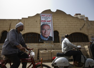An Egyptian man rides his bicycle near a poster of a presidential candidate in Cairo yesterday