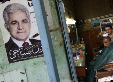 A campaign poster with the picture of Shafiq outside a barbershop in Cairo.