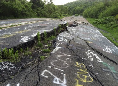 This is the road into Centralia, pictured just last week. It is buckled and broken from the fire which has raged in coal mine shafts under the town for the past 50 years. Tourists have left the graffiti on the road.