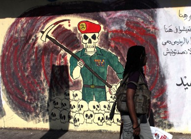 An woman passes by a wall with graffiti depicting the ruling military council and Arabic that reads,