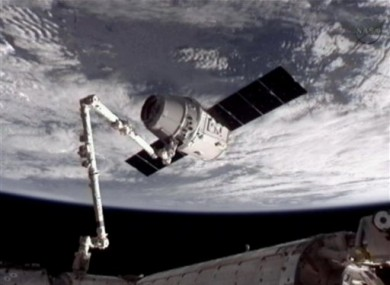 This image provided by NASA-TV shows the SpaceX Dragon commercial cargo craft, top, after it was grabbed by a robotic arm at the ISS.