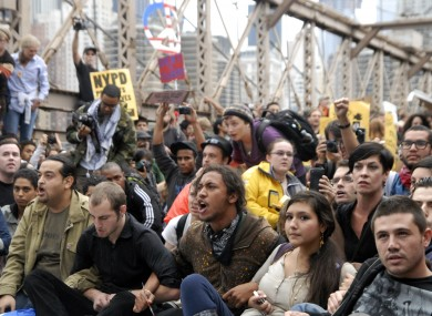 Protesters sit with arms linked on New York's Brooklyn Bridge before police began making arrests during a march by Occupy Wall Street on 1 October 2011