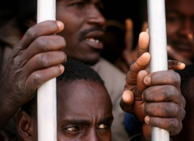 In this Saturday, Feb. 24, 2012 photo, illegal African migrants and suspected mercenaries stand in a prison in Gherian, Libya