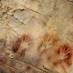 This undated handout photo shows detail of the 'Panel of Hands', El Castillo Cave, Spain, showing red disks and hand stencils made by blowing or spitting paint onto the wall. (AP Photo/Pedro Saura, AAAS)