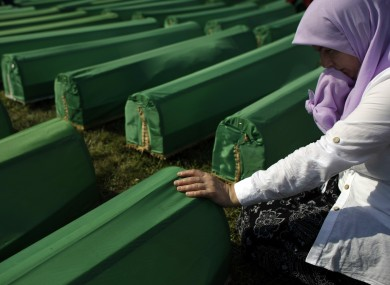 A woman touches the coffin of her relative among the over six-hundred displayed at the Potocari memorial cemetery near Srebrenica