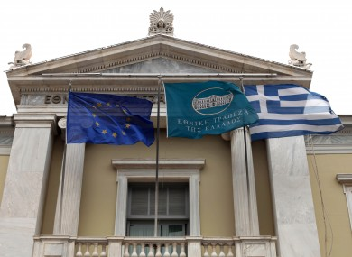 The flags of the EU and Greece fly outside the National Bank of Greece, alongside the bank's own flag, in Athens.