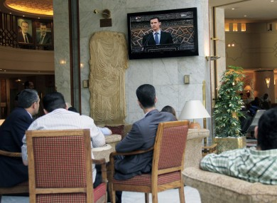 People watch Syrian president Bashar Assad deliver a live speech in Damascus, Syria, earlier today.