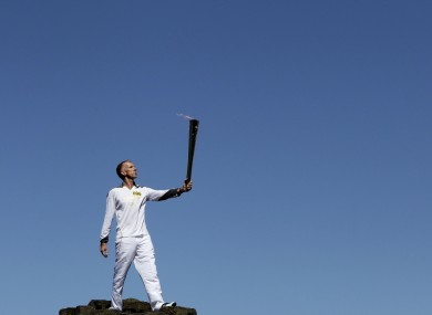 Peter Jack holds the Olympic torch aloft at the Giant's Causeway in county Antrim on Monday.