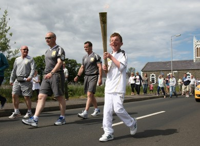 Torchbearer 020 Kiernan McLaughlin carries the Olympic Flame on the Torch Relay leg between Bellarena and Greysteel.