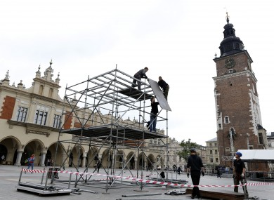 Workers build a stage area in the main square, ahead of the Euro 2012 kick-off, in Krakow today.