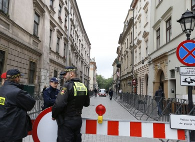 Security personnel keep guard at the entrance to the street where the England team hotel is located in Krakow.