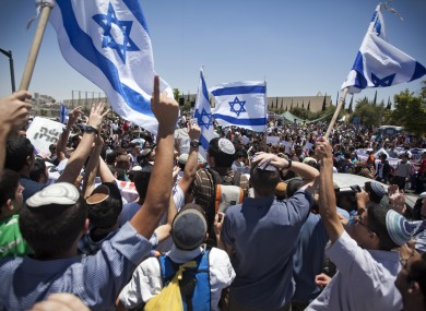 Jewish settlers wave Israeli flags during a protest against the decision to evacuate a West Bank outpost in the Ulpana neighbourhood.